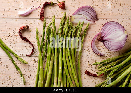 high-angle shot of a bunch of wild asparagus and half onion on a rustic wooden surface - Stock Photo