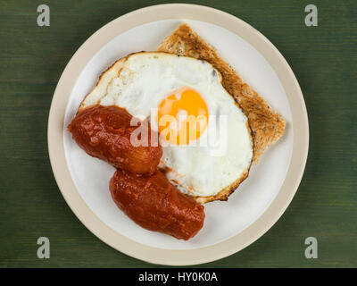 Fried Egg and Tomatoes on Toast on a Plate Against a Green Background - Stock Photo