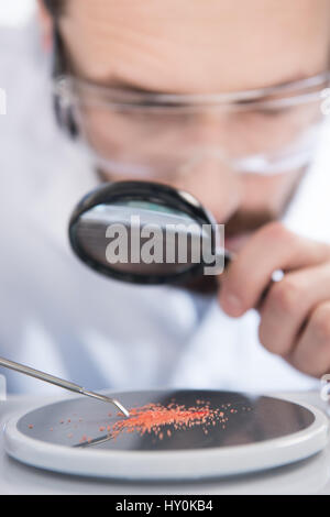 Close-up view of scientist looking at chemical sample through magnifying glass - Stock Photo