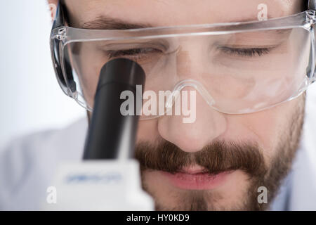 Close-up view of young man in protective glasses looking in microscope - Stock Photo