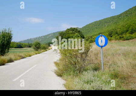 road sign for mounting snow chains is along an overgrown road on a summer day - Stock Photo