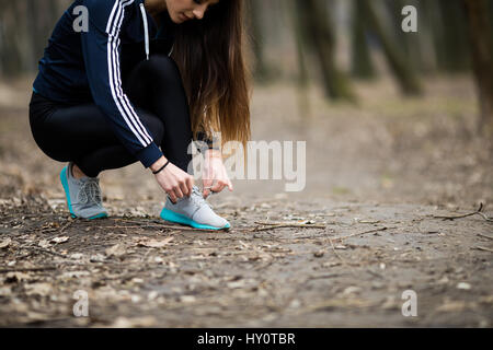 Young woman tying laces of running shoes before training - Stock Photo