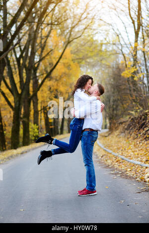Portrait of young loving couple kissing in autumn park - Stock Photo