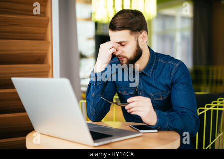 Feeling exhausted. Frustrated young beard man massaging his nose and keeping eyes closed while sitting at his working - Stock Photo