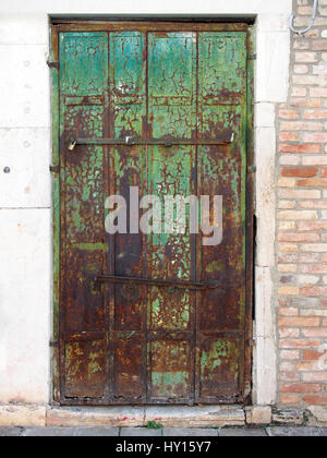 Old wooden green door with peeling paint and rusting hinges in an ancient brick wall - Stock Photo