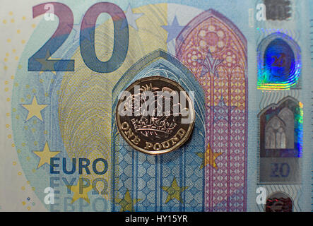 New twelve-sided one pound coin introduced end of March 2017 in UK - shown on 20 Euro banknote - Stock Photo