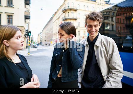 Sweden, Uppland, Stockholm, Kungsholmen, Young people standing in street talking - Stock Photo