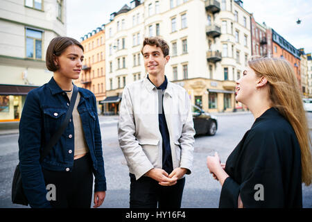 Sweden, Uppland, Stockholm, Kungsholmen, Young people talking in street - Stock Photo