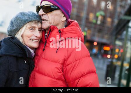 Sweden, Stockholm, Sodermalm, Senior couple hugging at bus stop - Stock Photo