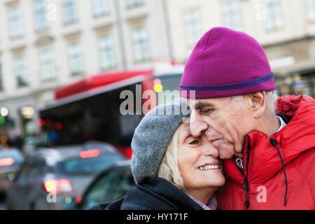 Sweden, Stockholm, Sodermalm, Senior couple hugging in street - Stock Photo