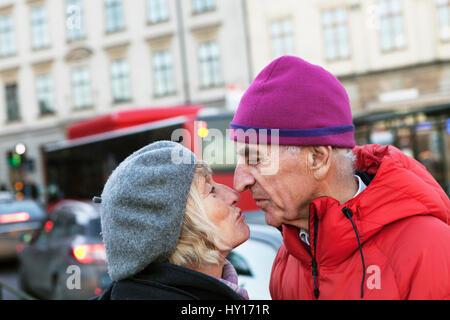 Sweden, Stockholm, Sodermalm, Senior couple kissing in street - Stock Photo