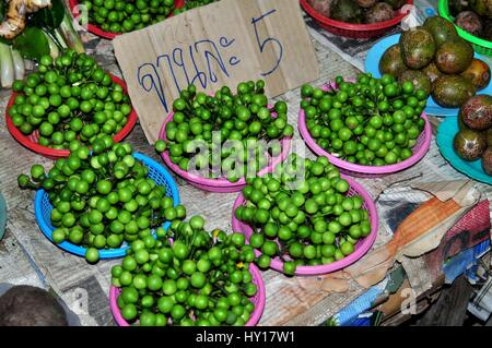 Lamphun, Thailand - December 28, 2012:  Dishes of green Makhan, small Asian eggplants, are displayed in dishes at - Stock Photo