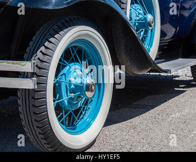 spoked wheels painted aqua blue with white wall tires on a vintage automobile stock