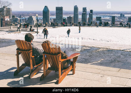 Montreal, CA - 30 March 2017: People sitting on a wooden lawn chair and enjoying a sunny spring day on Kondiaronk - Stock Photo
