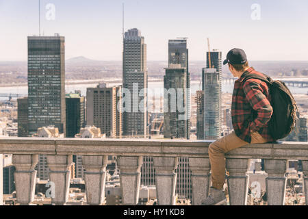 Montreal, CA - 30 March 2017: Young man sitting on parapet and looking at Montreal skyline from Kondiaronk Belvedere - Stock Photo