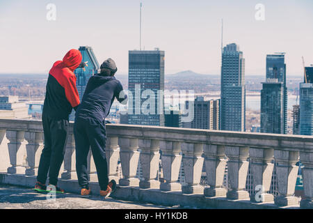 Montreal, CA - 30 March 2017: Two men looking at Montreal skyline from Kondiaronk Belvedere - Stock Photo