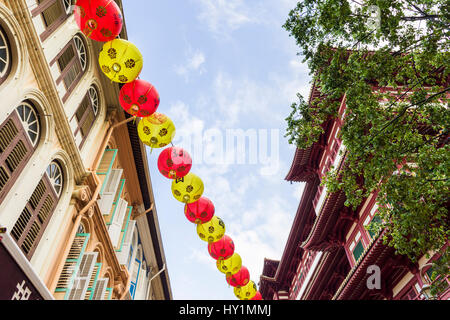 Traditional lanterns hang above shophouses in Singapore's Chinatown, next to the Buddha Tooth Relic Temple and Museum, - Stock Photo