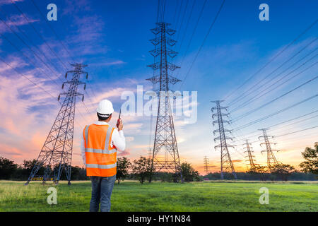 Electrical engineer with high voltage electricity pylon at sunrise background - Stock Photo