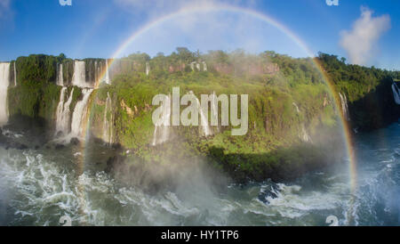 Rainbow over Iguasu Falls, on the Iguasu River, Brazil / Argentina border, from the Brazilian side. State of Parana, - Stock Photo