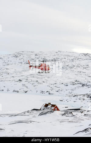 A tourist helicopter landing in the tiny inuit settlement of Oqaatsut in west Greenland - Stock Photo