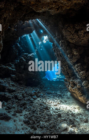 Shafts of light shine through darkness of cavern within  coral reef. Sha'ab Claudia, Fury Shoal, Egypt. Red Sea. - Stock Photo