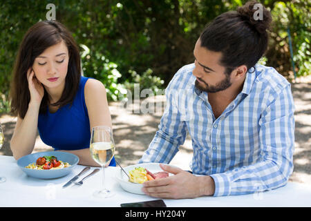 Young couple having relationship difficulties at outdoor restaurant - Stock Photo