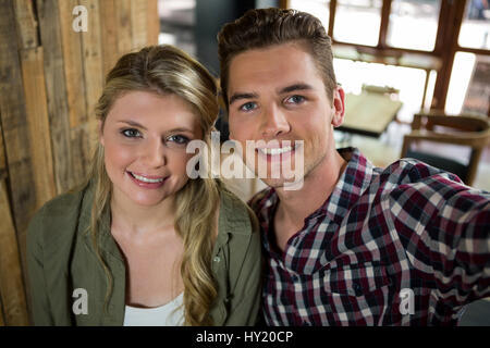 Portrait of smiling young couple posing in coffee shop - Stock Photo
