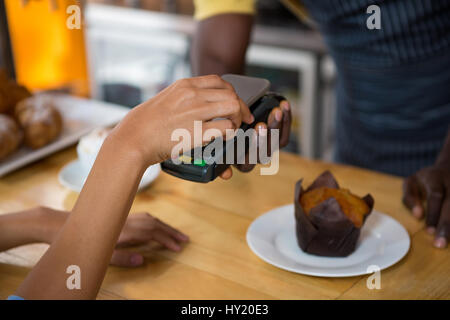 Cropped image of customer paying barista through smart phone in coffee shop - Stock Photo