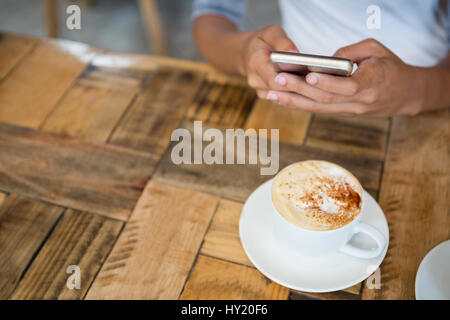 High angle view of woman using mobile phone with coffee cup on table at cafe - Stock Photo