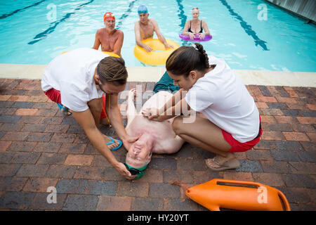 High angle view of rescue workers helping unconscious senior man at poolside - Stock Photo