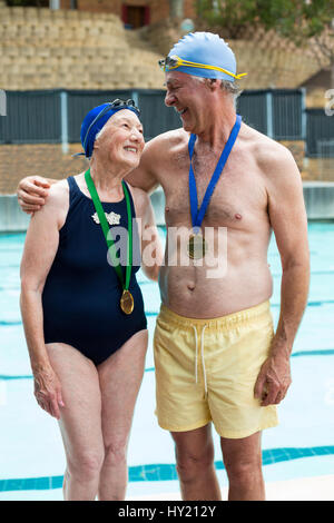 Happy senior couple wearing medals while standing at poolside - Stock Photo