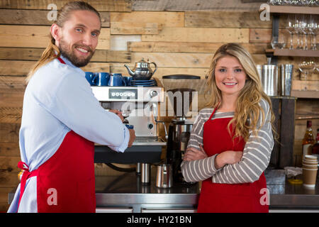 Portrait of male and female baristas standing by coffee machine at cafeteria - Stock Photo