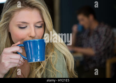 Close-up of young woman drinking coffee in cafeteria - Stock Photo