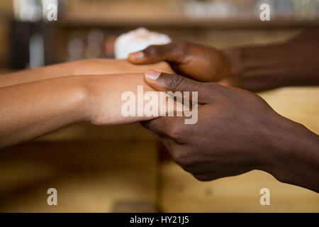 Close-up of multi ethnic couple holding hands in coffee house - Stock Photo