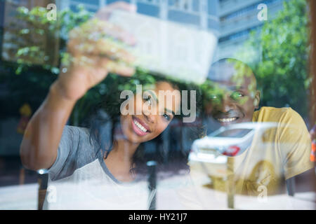 Smiling young couple taking selfie with cellphone in coffee shop seen through window - Stock Photo