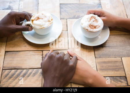 High angle view of couple having coffee while holding hands in cafe