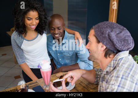 Young man showing mobile phone to couple at table in coffee shop - Stock Photo