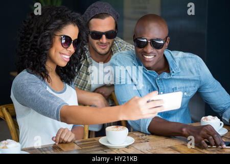 Happy multi ethnic friends wearing sunglasses while taking selfie in coffee shop - Stock Photo