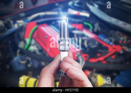 Mechanic holds a spare part spark plug in his hand. Auto part spark plug close-up. - Stock Photo