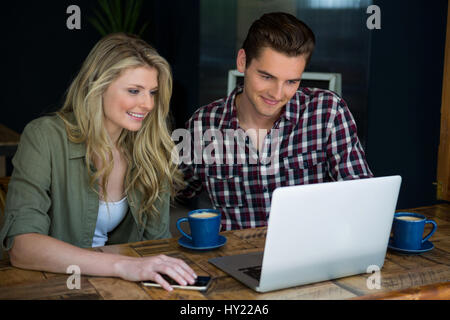 Smiling young couple using laptop at table in cafeteria - Stock Photo