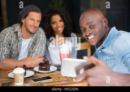 Happy man with friends taking selfie at wooden table in coffee shop - Stock Photo