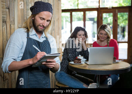 Male barista writing orders with female customers in background at coffee shop - Stock Photo