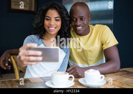 Smiling young couple taking selfie with cellphone in coffee shop - Stock Photo