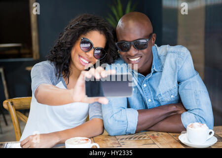 Smiling young couple taking selfie with smart phone in coffee shop - Stock Photo