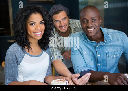 Portrait of multi ethnic male and female friends with mobile phone in coffee shop - Stock Photo