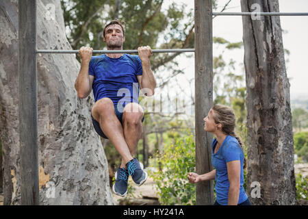 Fit man and woman performing pull-ups on bar during obstacle course in boot camp - Stock Photo