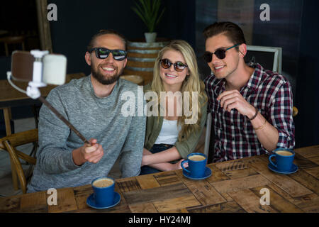 Happy friends taking selfie with monopod at table in coffee shop - Stock Photo