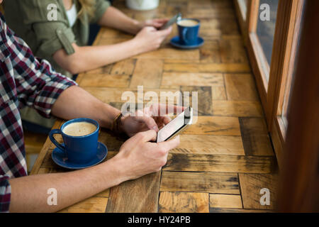 Cropped image of man and woman using mobile phones in coffee shop - Stock Photo