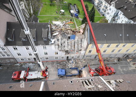 Dortmund, Germany. 1st Apr, 2017. Cranes stand in front of an apartment building which was destroyed in an explosion - Stock Photo