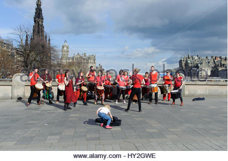 Edinburgh, UK. 1 April, 2017.  UK Weather.  A small child drops coins in a collection for a drumming group performing - Stock Photo